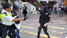 Polisi (kiri) menembak seorang demonstran prodemokrasi (kanan) saat terjadi protes di Distrik Sai Wan Ho, Hong Kong, Senin (11/11/2019). Aksi penembakan yang dilakukan polisi tersebut tersiar secara langsung lewat layanan streaming Facebook. (LAURENT FIEVET/CUPID NEWS/AFP)