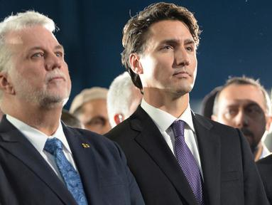 Perdana Menteri (PM) Kanada, Justin Trudeau (kanan) bersama Wali Kota Quebec, Philippe Couillard menghadiri upacara pemakaman tiga dari enam korban penembakan di Masjid Quebec, di Montreal Olympic, Kamis (2/2). (Paul Chiasson/The Canadian Press via AP)