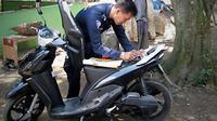 Petugas Samsat melakukan cek fisik terhadap kendaraan milik warga. Hal ini merupakan terobosan terbaru Samsat Polda Tangerang dengan cara mendatangi wajib pajak. (Antara)