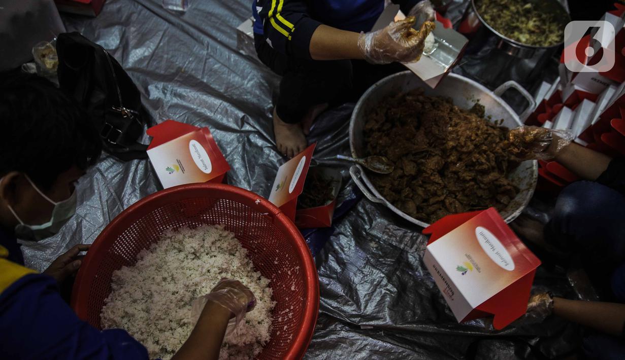 Petugas Taruna Siaga Bencana (Tagana) menyiapkan nasi kotak di Dapur Umum Kementerian Sosial Peduli Dampak Covid-19 di Kompleks Gedung Konvensi TMP Nasional-Utama, Kalibata, Jakarta, Rabu (8/4/2020). Dalam sehari, petugas menyiapkan 5.000 hingga 9.000 paket nasi bungkus. (Liputan6.com/Faizal Fanani)