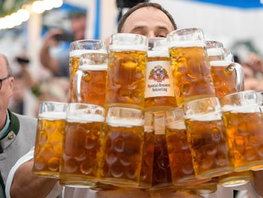 Oliver Struempfel membawa gelas bir sebanyak-banyaknya sambil berjalan untuk memecahkan rekor saat bersaing pada festival tradisional Gillamoos di Abensberg, Jerman, Minggu (3/9). Struempfel berhasil menyusun 29 gelas bir besar. (Matthias Balk/dpa via AP)