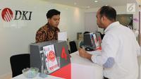 Teller Bank DKI sedang melayani nasabah pada Hari Batik Nasional di cabang Jakarta Pusat (02/10). Bank yang memiliki 236 kantor layanan menginstrusikan seluruh karyawan mengenakan baju batik. (Liputan6.com/Pool)