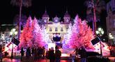 Orang-orang mengunjungi lampu dan dekorasi untuk menyambut Natal yang menghiasi depan Kasino Monte-Carlo di Monako pada 7 Desember 2018. (Photo by VALERY HACHE / AFP)