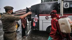 Petugas pemadam kebakaran menyemprotkan disinfektan kepada penumpang bus AKAP di Terminal Kampung Rambutan, Jakarta, Minggu (23/5/2021). Penyemprotan rutin dilakukan kepada bus AKAP dan penumpang selama arus mudik Lebaran sebagai langkah mencegah penyebaran Covid-19. (merdeka.com/Iqbal S Nugroho)