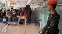 Personil TNI AU menjaga situasi dan kondisi arus mudik di Bandara Halim Perdanakusuma Jakarta, Senin (4/7). H-2 jelang Idul Fitri 1437 H, ribuan calon penumpang diberangkatkan dari Bandara Halim Perdanakusuma. (Liputan6.com/Helmi Fithriansyah)