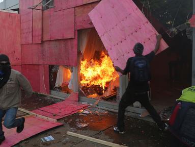 Demonstran mengamuk membakar gedung Kementerian Pertanian dalam unjuk rasa anti-pemerintah di Brasilia, Brasil, Rabu (24/5). Ribuan demonstran bergerak ke ibu kota menuntut pengunduran diri Presiden Michel Temer. (AP Photo/Eraldo Peres)