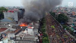 Foto udara kebakaran yang melanda permukiman padat penduduk di kawasan Tanah Tinggi, Johar Baru, Jakarta, Selasa (26/6). Kebakaran terjadi di rumah tinggal padat hunian di Jalan Tanah Tinggi 1 Johar Baru, Jakarta Pusat. (Liputan6.com/Arya Manggala)