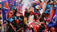 Massa buruh menyalakan suar saat aksi perayaan MayDay di Jalan Medan Merdeka Barat, Senin (5/1). Ribuan massa buruh turun ke jalan dalam perayaan Hari Buruh Internasional. (Liputan6.com/Helmi Fithriansyah)