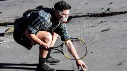 Seorang demonstran membawa raket tenis mengambil batu saat bentrok dengan polisi anti huru hara selama memprotes kebijakan ekonomi pemerintah di Santiago (6/11/2019). para pemrotes meminta para demonstran untuk memperluas aksi unjuk rasa. (AFP Photo/Martin Bernetti)