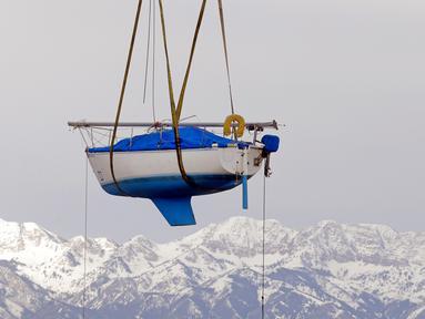 Sebuah perahu layar diangkat untuk dipindahkan ke Great Salt Lake, Utah (6/4). Sebelumnya perahu ini selama dua tahun tidak digunakan karena pantai Utah dilanda kekeringan. (AP Photo / Rick Bowmer)