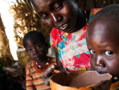 Seorang wanita bernama Nybol Madut memberi minum semangkuk alkohol lokal kepada anaknya di tempat penampungan di Sudan Selatan (22/11). (AFP Photo/Albert Gonzalez Farran)