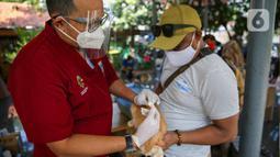 Paramedis dari pusat kesehatan hewan (Puskeswan) Dinas Ketahanan, Pertanian, dan Perikanan Kota Adm. Jakarta Selatan menyuntikkan vaksin anti rabies secara gratis di kawasa Tebet, Jakarta, Sabtu (31/10/2020). (Liputan6.com/Faizal Fanani)