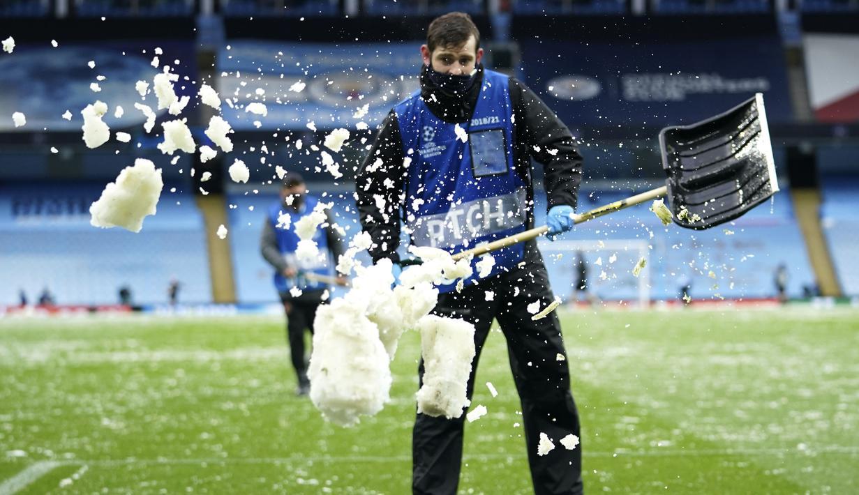 Petugas membuang salju yang menutupi rumput ke pinggir lapangan jelang laga Manchester City melawan PSG pada laga semifinal Liga Champions di Stadion Etihad, Rabu (5/5/2021). (AP/Dave Thompson)