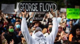 Seorang pria memegang skateboard bertuliskan nama George Floyd ketika berunjuk rasa dalam mendukung Floyd dan Regis Korchinski-Paquet dan protes terhadap rasisme, ketidakadilan dan kebrutalan polisi, di Vancouver (31/5/2020). (Darryl Dyck/The Canadian Press via AP)