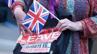 """Pendukung Brexit memegang poster dan bendera Inggris di Westminster, London, Kamis (23/6). Perhitungan suara hasil Referendum Brexit menunjukkan mayoritas rakyat Inggris memilih """"Brexit"""" alias keluar dari Uni Eropa. (REUTERS/Toby Melville)"""