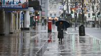 """Seorang wanita melintas di jalan dekat Leicester Square, London, Inggris, 21 Desember 2020. Pada Minggu (20/12), Menteri Kesehatan Inggris Matt Hancock memperingatkan bahwa galur baru COVID-19 """"tidak terkendali"""" di Inggris. (Xinhua/Han Yan)"""
