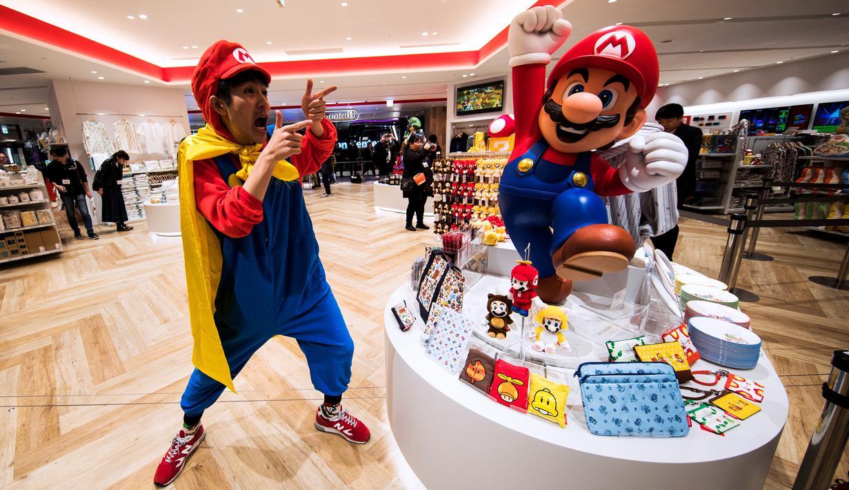 Seorang pria mengenakan kostum salah satu tokoh ikonik dari Nintendo, Mario berpose di sebelah merchandise yang berkaitan dengan permainan ini selama pratinjau pers di toko baru Nintendo di Tokyo, 19 November 2019. Nintendo akan meresmikan toko pertamanya di Tokyo pada pekan ini. (Behrouz MEHRI/AFP)