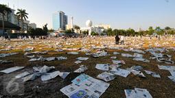 Lembaran koran bekas alas salat memenuhi lapangan Masjid Agung Al Azhar, Jakarta usai pelaksanaan salat Idul Fitri 1436 H, Jumat (17/7/2015). Sisa koran bekas akan dikumpulkan dan dimanfaatkan oleh pemulung. (Liputan6.com/Yoppy Renato)