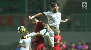 Pemain belakang Indonesia U-23, Gavin Kwan Adsit (kanan) berebut bola dengan pemain Korea Utara pada laga PSSI Anniversary Cup 2018 di Stadion Pakansari, Kab Bogor, Senin (30/4). Laga kedua tim berakhir imbang 0-0. (Liputan6.com/Helmi Fithriansyah)