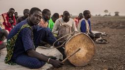Penggembala dari suku Dinka bermain alat musik di kamp ternak mereka di Mingkaman, Lakes State, Sudan Selatan, Minggu (4/3). Mereka akan mendirikan kamp ternak besar untuk memastikan hewan mereka dekat dengan air. (Stefanie GLINSKI/AFP)