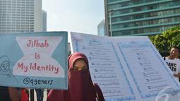 Seorang perempuan berdiri di depan Alquran raksasa yang dibawa mengelilingi Bundaran HI, Jakarta, Minggu (21/12/2014). (Liputan6.com/Herman Zakharia)