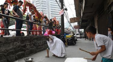Anggota kelompok barongsai melihat aksi anak-anak melakukan tarian singa di distrik Chinatown, Manila (4/2). Anak-anak jalanan ini tampil lucu dengan alat seadanya seperti ember dan kerdus untuk menyambut Tahun Baru Imlek. (AFP Photo/Ted Aljibe)