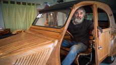 Seorang pensiunan tukang lemari, Michael Robillard, duduk di replika mobil legendaris Citroen 2CV dari kayu di bengkel kerjanya di Loches, Prancis, 21 Maret 2017. Mobil klasik itu dibuat dengan skala sesungguhnya atau 1:1. (GUILLAUME SOUVANT/AFP)