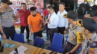 Salah satu tersangka pembobolan minimarket di Pekanbaru menunjukkan ke polisi bagaimana mencongkel gembok. (Liputan6.com/M Syukur)