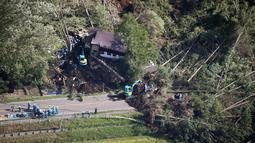 Petugas mencari korban yang selamat dari sebuah bangunan yang roboh akibat tanah longsor yang disebabkan oleh gempa di Kota Atsuma, Hokkaido, Jepang, Kamis (6/9). Akibat tanah longsor tersebut dua orang tewas dan puluhan hilang. (Kyodo News via AP)