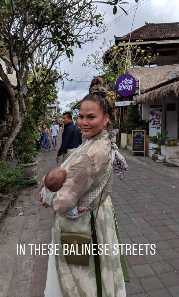 Bisa jalan-jalan dengan santai menyusuri setiap sudut Ubud, Bali, hot mom cantik ini tampak membiarkan baby Miles terlelap dalam gendongannya./Copyright instagram.com/chrissyteigen/johnlegend