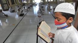 Santri berusia belasan tahun membaca Al quran atau tadarus bersama-sama dengan menerapkan jaga jarak di Masjid Daarul Qu'ran Pesantren Al Kautsar, Cibinong, Bogor, Kamis (7/5/2020). Kegiatan Khatam Al quran tersebut dilakukan rutin di setiap bulan Ramadan. (merdeka.com/Arie Basuki)
