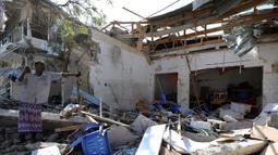 Seorang pria berdiri di tengah reruntuhan bangunan yang hancur akibat ledakan bom mobil di Mogadishu, Somalia (28/3). Insiden tersebut telah menyebabkan 11 orang tewas dan belasan lainnya terluka. (Reuters/Feisal Omar)