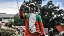 Petugas Sudin LH menunjukkan masker yang ditemukan di Dipo Sampah Kecamatan Pademangan, Ancol, Jakarta, Rabu (24/2/2021). Dengan berbekal alat pemilah, sarung tangan, dan masker, jasa mereka patut dihargai dalam membersihkan lingkungan dari limbah medis. (merdeka.com/Iqbal S. Nugroho)