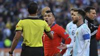 Pemain Timnas Argentina, Lionel Messi (kanan) berbicara dengan wasit setelah diganjar kartu merah saat melawan Chile pada perebutan tempat ketiga Copa America 2019 di Corinthians Arena, Sao Paolo, Minggu (7/7/2019) dini hari WIB. (AFP/Nelson Almeida)