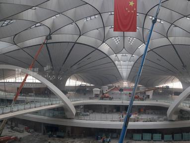 Sebuah bendera nasional Tiongkok digantung di terminal Bandara Internasional Beijing Daxing yang sedang dibangun di pinggiran Beijing, China (1/3). Bandara baru di ibu Kota China ini akan menjadi salah satu yang terbesar di dunia. (AP Photo/Ng Han Guan)