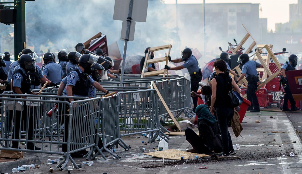 Polisi menyingkirkan barikade yang dibuat demonstran saat unjuk rasa atas kematian George Floyd oleh polisi di luar Third Police Precinct, Minneapolis, Minnesota, Amerika Serikat, Rabu (27/5/2020). Kematian George Floyd memicu kerusuhan di Minneapolis. (Kerem Yucel/AFP)