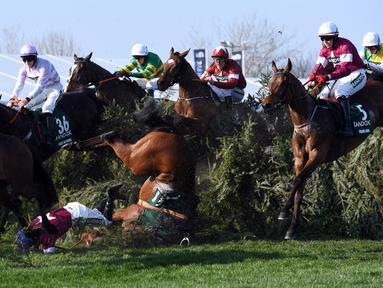 Seorang joki bernama Rachael Blackmore terjungkal bersama kudanya saat mengikuti pacuan kuda Grand National di Aintree Racecourse di Liverpool, Inggris (14/4). Rachael Blackmore mengalami cedera akibat insiden itu. (AFP/Paul Ellis)