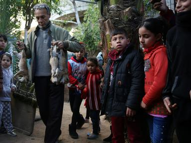 Pemilik kebun binatang Fathi Jumaa membawa mayat empat anak singa sebelum dikubur di kebun binatangnya di kamp pengungsi Rafah, Gaza (18/1). Fathi mengatakan ia menutupi sangkar singa-singa dengan selimut jelang badai musim dingin. (AP Photo/Adel Hana)