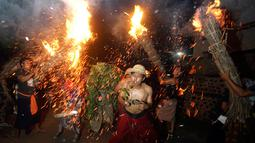 Sejumlah pria Bali melakukan ritual Lukat Gni di Klungkung, Bali (16/3). Tradisi turun temurun ini dilaksanakan setiap tahun pada rahina tilem sasih kasanga atau saat Pangrupukan, sehari menjelang perayaan Nyepi. (AP Photo / Firdia Lisnawati)