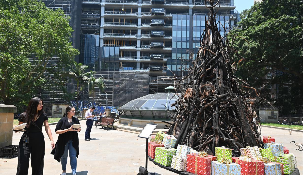 Dua wanita melihat instalasi yang dijuluki 'Pohon Natal yang Terbakar' di Sydney (18/12/2019). Instalasi Pohon Natal ini untuk mendukung Dana Bantuan dan Pemulihan Bencana Palang Merah Australia di tengah situasi kebakaran hutan. (AFP/Peter Parks)