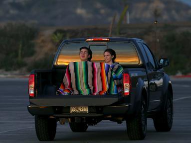 Pasangan muda berselimut menikmati keindahan matahari terbenam duduk di belakang mobil di Cardiff, California (27/1/2016). Wilayah Selatan California ini usai di landa Badai El Nino. (REUTERS/Mike Blake)