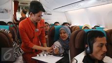 Pramugari membagikan cokelat kepada penumpang dalam penerbangan di Pesawat Garuda Indonesia menuju, Padang, Sumatera Barat, Jumat (21/4). Dalam rangka menyambut Hari Kartini, penerbangan Garuda Indonesia diawaki oleh perempuan. (Liputan6.com/Angga Yuniar)