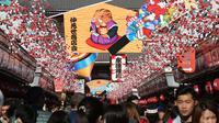 Pejalan kaki melintas di bawah dekorasi shio babi tanah yang mengarah ke kuil Buddha Asakusa Sensoji di Tokyo, Jepang, Kamis (27/12). Tahun babi tanah 2019 akan penuh sukacita cocok untuk persahabatan dan cinta semua shio. (AP Photo/Koji Sasahara)