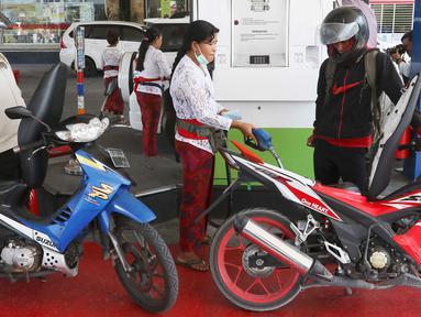 Petugas dengan pakaian adat mengisi bahan bakar minyak (BBM) untuk sepeda motor di SPBU, Bali, Rabu (10/10). Petugas SPBU mengenakan pakaian adat Bali untuk menyambut pertemuan tahunan IMF dan Bank Dunia. (Liputan6.com/Angga Yuniar)