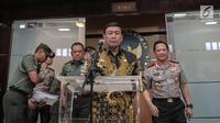 Menko Polhukam Wiranto (tengah) didampingi Panglima TNI Jenderal TNI Gatot Nurmantyo (kiri) dan Kapolri Jenderal Pol Tito Karnavian (kanan) bersiap memberi keterangan usai rapat di Kemenkopolhukam, Jakarta, Jumat (6/10). (Liputan6.com/Faizal Fanani)