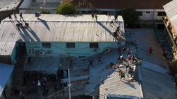 Narapidana melemparkan batu ke arah polisi dari atap penjara Tacumbu saat kerusuhan di Asuncion, Paraguay, Selasa (16/2/2021). Tidak disebutkan bagaimana enam narapidana tewas dalam kerusuhan tersebut, tetapi media lokal melaporkan bahwa tiga dari mereka dipenggal. (AP Photo/Jorge Saenz)