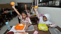 Sejumlah siswi menunjukkan salah satu menu makanan tambahan saat program Penyediaan Makanan Tambahan Anak Sekolah (PMTAS) di SD Negeri 01 Tanjung Priok, Jakarta, Kamis (28/3).  (merdeka.com/Iqbal S. Nugroho)