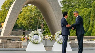 Presiden AS Barrack Obama dan Perdana Menteri Jepang Shinzo Abe berjabat tangan setelah meletakkan karangan bunga di cenotaph di Taman Peringatan Perdamaian Hiroshima pada 27 Mei 2016. (AP Images)