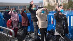 Pasien yang telah sembuh melambaikan tangan saat berjalan keluar dari rumah sakit sementara Wuchang di Wuhan, 10 Maret 2020. Dua rumah sakit sementara terakhir di Wuhan ditutup pada hari itu yang sekaligus menandai penutupan seluruh 16 rumah sakit sementara di kota tersebut. (Xinhua/Xiao Yijiu)