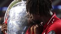 Penyerang Liverpool, Divock Origi, mencium trofi usai menjuarai Liga Champions 2019 di Stadion Wanda Metropolitano, Madrid, Minggu (2/6). Liverpool menang 2-0 atas Tottenham Hotspur. (AP/Manu Fernandez)